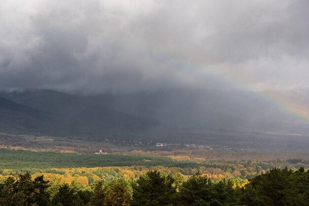 Mening van een van een regenboog over bergachtig landschap in de herfst met een stormachtig klimaat