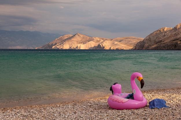 Mening van een zwemmende opblaasbare ring met flamingodesign op het strand van baska, kroatië
