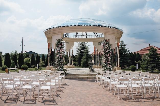 Mening van gastzetels en ceremoniële huwelijksboog op zonnig zeg, chiavari-stoelen, verfraaid gebied