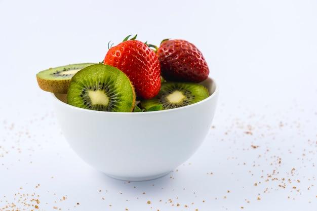 Mening van gesneden kiwi's en aardbeien in een witte kom op wit met bruine suiker