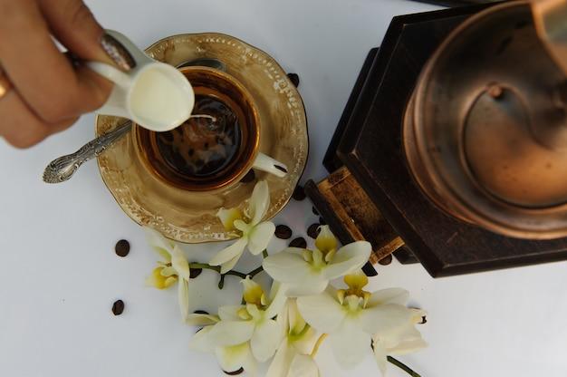 Mening van hierboven over de kop van koffie waarin gietende melk op de witte lijst