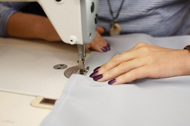 Mening van hierboven over handen van vrouwelijke kleermaker die aan naaimachine werken. kledingindustrie
