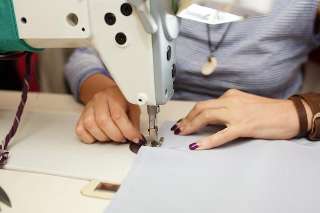 Mening van hierboven over handen van vrouwelijke kleermaker die aan naaimachine werken