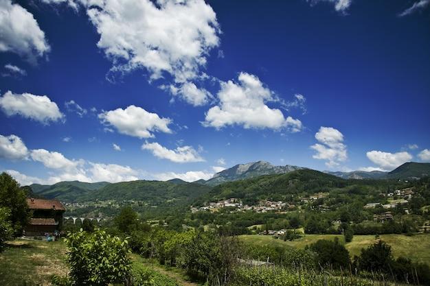 Mening van huizen op groene heuvels met een bewolkte blauwe hemel op de achtergrond
