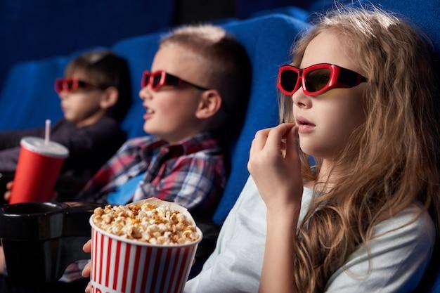 Mening van kant van meisje dat 3d glazen draagt die popcorn eten
