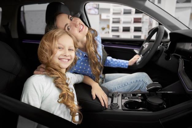 Mening van kant van mooie meisjeszitting in nieuwe auto met moeder