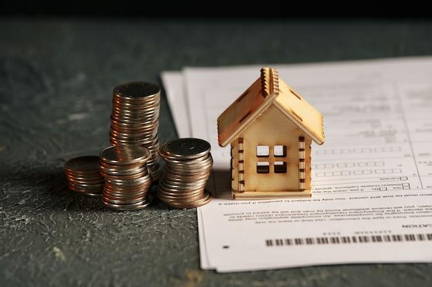 Mening van muntstukstapel met huismodel op groen