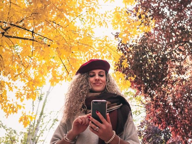 Mening van onderaan van een jonge glimlachende vrouw die haar smartphone met een rode en gele daling gebruiken
