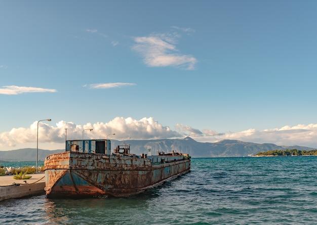 Mening van oude roestige argosy dichtbij pijler in ionische overzees. mooi landschap van het eiland corfu, bergen op een zonnige dag.