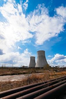 Mening van rokende schoorstenen van kerncentrale, hoogspanningslijnen en bos, onder blauwe hemel met witte wolken