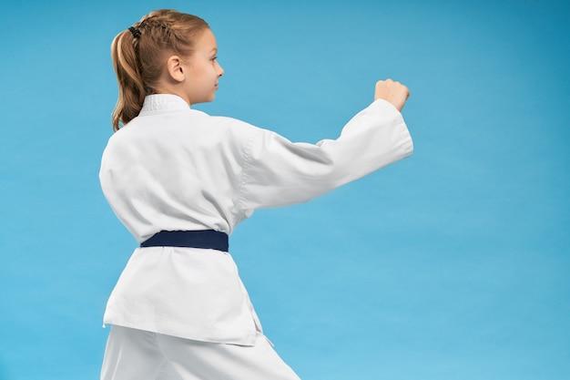 Mening van rug van meisje dat karate op geïsoleerde achtergrond doet