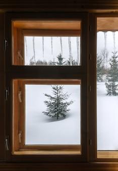 Mening van sneeuwweer van binnenuit het huis door houten venster met hangende ijspegel op het dak