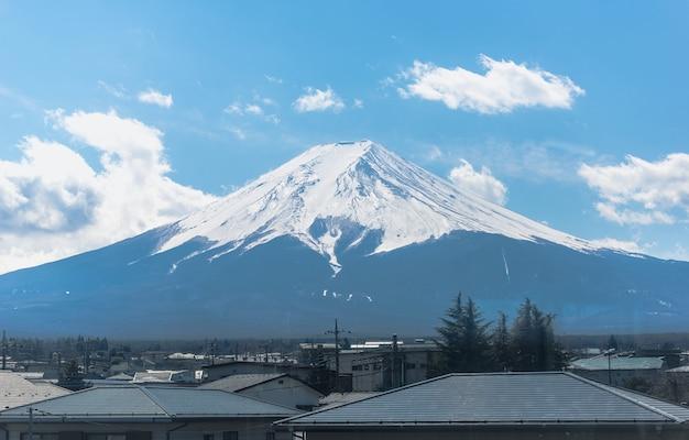 Mening van treinvenster met onderstel fuji op blauwe hemelachtergrond.