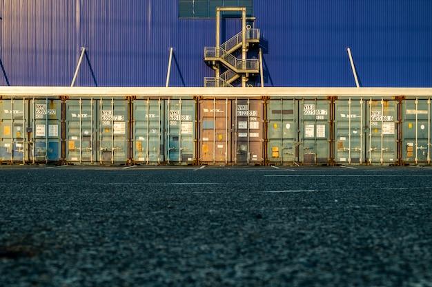 Mening van vele het verschepen containersdeuren met brandtrapachtergrond.