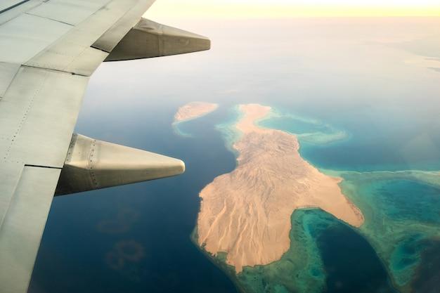 Mening van vliegtuig op de vliegtuigen witte vleugel die over oceaanlandschap vliegen in zonnige ochtend. vliegreizen en transport concept.