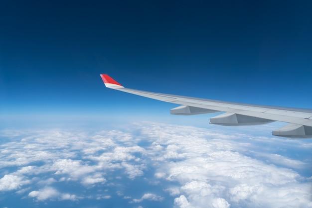 Mening van vliegtuigvenster met blauwe hemel en witte wolken