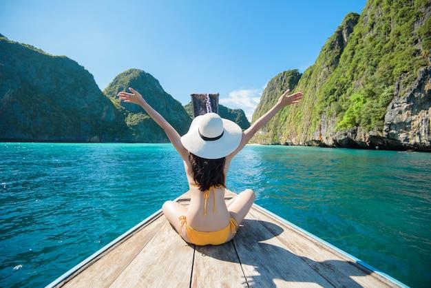 Mening van vrouw die in zwempak op thaise traditionele longtailboot genieten over mooie berg en oceaan, phi phi-eilanden, thailand