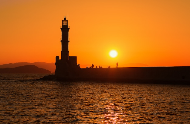 Mening van vuurtoren in overzees in chania, kreta, griekenland. silhouetten tegen ondergaande zon.