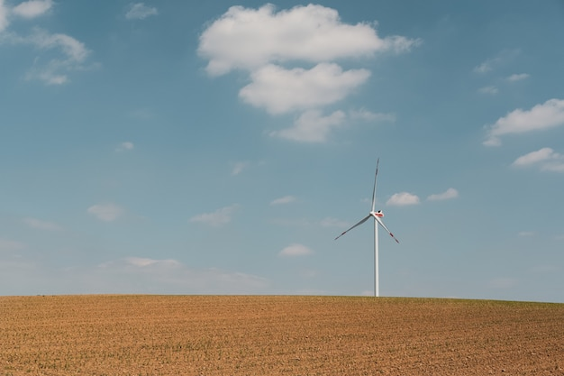 Mening van windturbine en bruin landbouwbedrijf onder de blauwe hemel en witte wolken