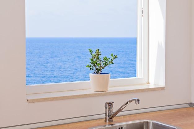 Mening van zeegezicht door een open venster in keuken