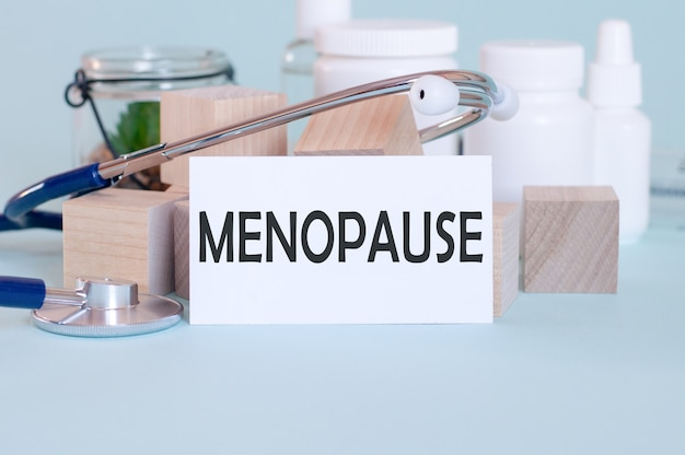 Menopauze woorden geschreven op witte medische kaart, met stethoscoop, groene bloem, medische pillen en houten blokken