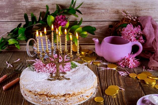 Menora met brandende kaarsen op de top van feestelijke taart