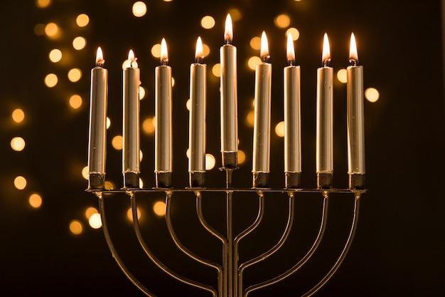 Menora met kaarsen dichtbij abstracte slingerlichten