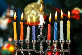 Menorah met kaarsen voor Hanukkah op de achtergrond van de boom van het nieuwe jaar