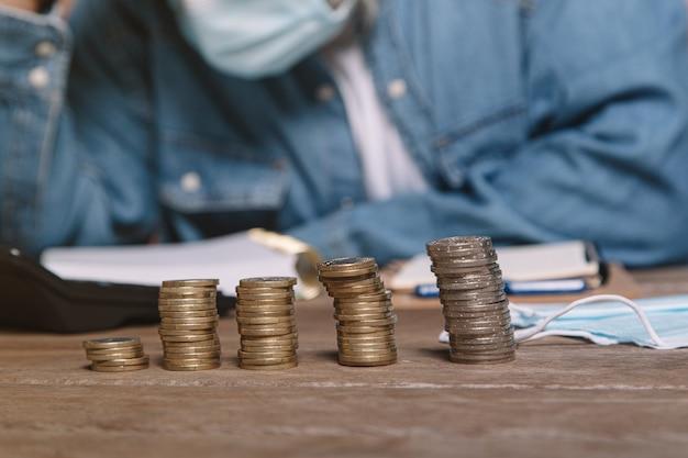 Mens aan bureau in denimoverhemd en hoofd van de maskerholding gefrustreerd door geld.
