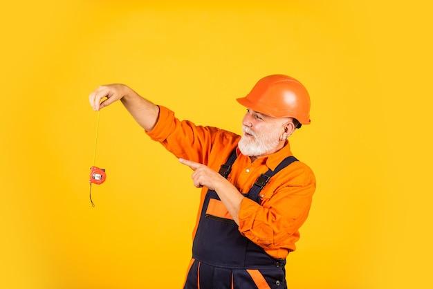 Mens aan het werk. bouw man houdt meetlint vast. techniek en reparatie. tevreden timmerman. klusjesman meten muur. senior bouwer gebruik tape-line voor maatregel. meting. ingenieur maat meten.
