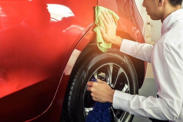 Mens aziatische inspectie en schoonmakende materiaalautowasserette met rode auto