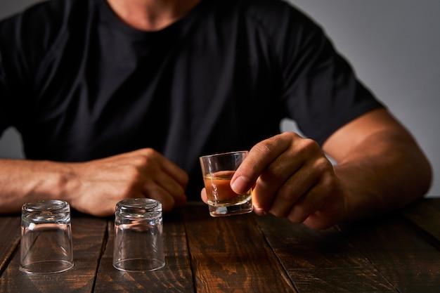 Mens bij een bar die alcohol in geschotene glazen drinkt. concept van alcoholisme en alcoholverslaving.