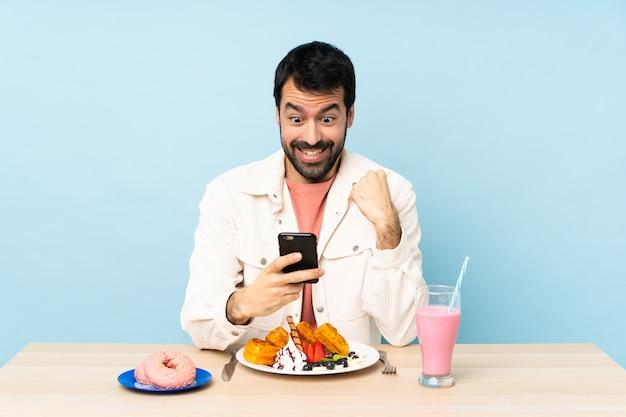 Mens bij een lijst die ontbijtwafels en een milkshake heeft verrast en een bericht verzendt