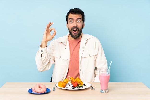 Mens bij een lijst die ontbijtwafels en een milkshake heeft verrast en ok teken toont