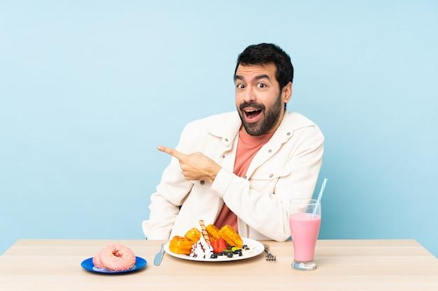 Mens bij een lijst die ontbijtwafels en een verraste milkshake heeft en kant richt