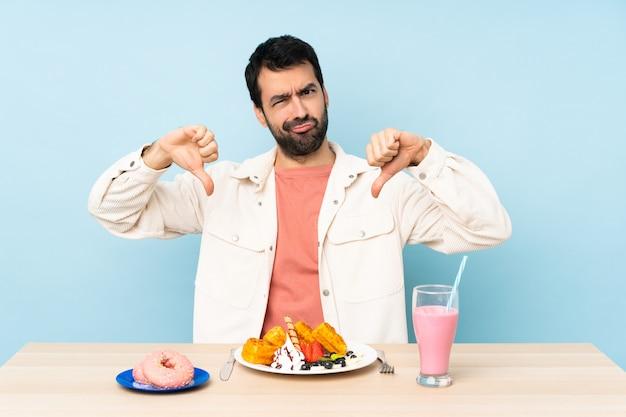 Mens bij een lijst die ontbijtwafels heeft en een milkshake die duim neer toont