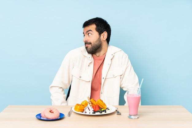 Mens bij een lijst die ontbijtwafels heeft en een milkshake die twijfelsgebaar maakt dat kant kijkt