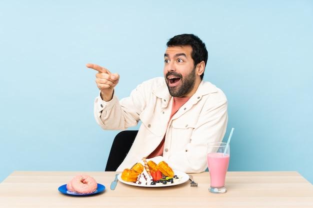 Mens bij een lijst die ontbijtwafels heeft en een milkshake die weg richt
