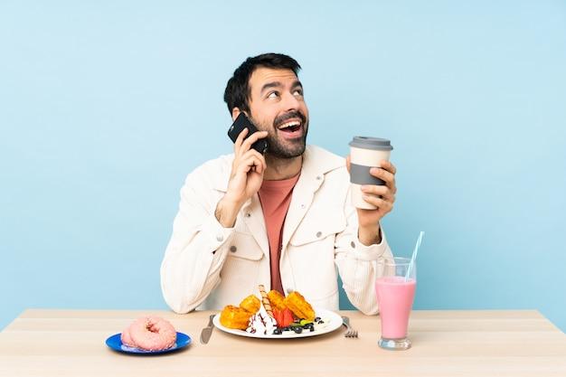 Mens bij een lijst die ontbijtwafels heeft en een milkshake holdingskoffie en mobiel meenemen
