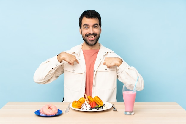 Mens bij een lijst die ontbijtwafels heeft en een milkshake met verraste gelaatsuitdrukking