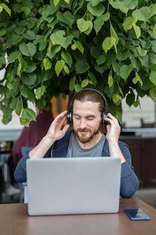 Mens bij een terras dat aan muziek op hoofdtelefoons met laptop luistert