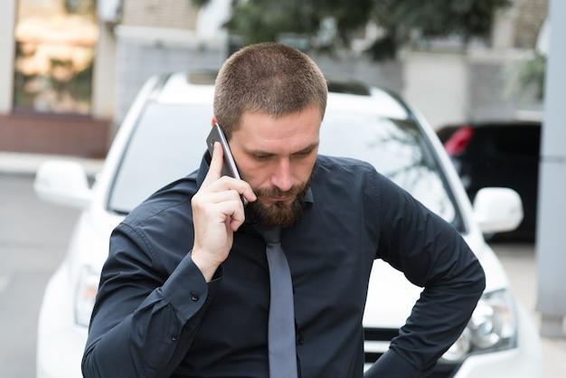 Mens dichtbij de auto die op de telefoon spreekt