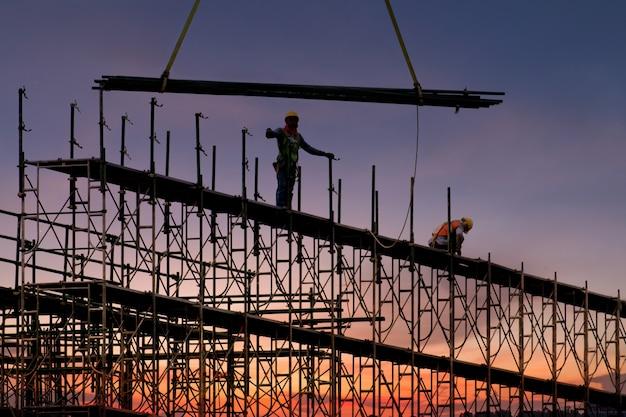 Mens die aan bouwwerf met steiger werkt en bouwt, steiger voor bouwfabriek
