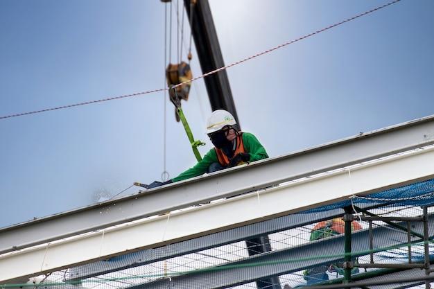 Mens die aan bouwwerf met steiger werkt en met zonachtergrond bouwt, steiger voor bouwfabriek