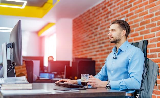 Mens die aan bureaucomputer met vele monitors op kantoor werkt