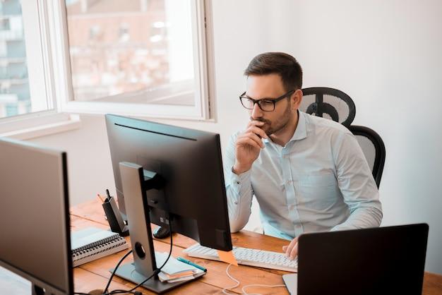 Mens die aan computer in modern bureaubinnenland werkt.