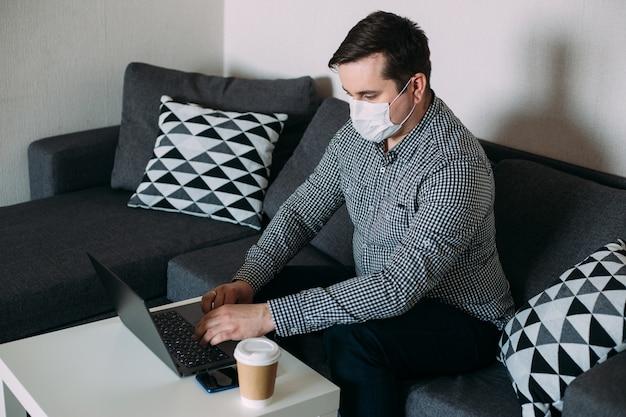 Mens die aan computer werkt die masker draagt