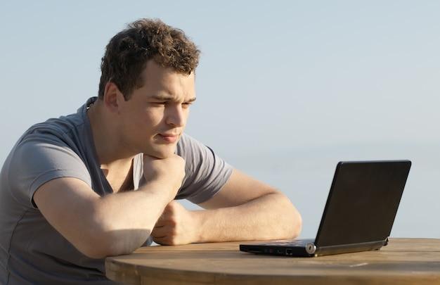 Mens die aan de vertoning van kleine laptop computer kijkt