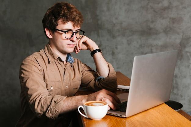 Mens die aan laptop in het bureau werkt