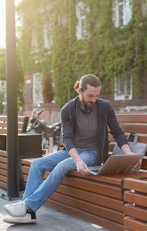 Mens die aan laptop in openlucht in de stad werkt